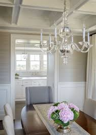 white on the bottom light gray on the top covered with wainscoting on the  lower half and gray grasscloth on the upper half and ivory curtains hang in  the ...