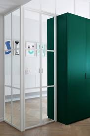 Colourful cabinetry offsets white interior of Bauhaus apartment in ...
