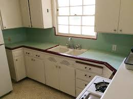 yn s kitchen looks pretty adorable in these photos but she told us that 60 year old tile countertop has twisted ed and the wood underneath has