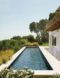 a simple modern narrow pool with a gorgeous view and a deck next to it