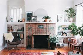 fresh living room in a small space with cozy armchair and brick fireplace also round mirror