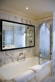 Bathroom mirror TV above marble bathtub