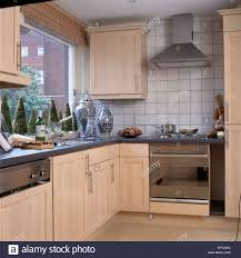 Small Fitted Kitchen Stainless Steel Extractor Above White Oven In Small Modern Kitchen