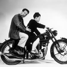 the eames office. charles und ray eames auf einem velocettemotorrad im office and the