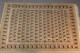 a fine handmade cream color lambs wool persian rug with an allover paisley pattern