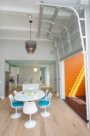 elegant extendable dining table in dining room beach style with interior garage door next to midcentury modern kitchen alongside cool garage and garage