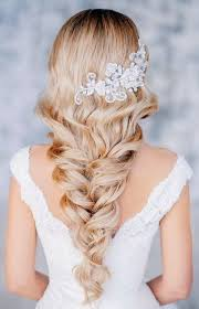 soft curls woven into a loose braid for brides with long hair by elstile the