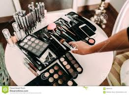 hands of a makeup artist many cosmetics and brushes on a table in the salon