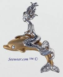 white gold mermaid riding atop a 14kt gold dolphin with diamonds
