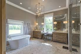the bathroom is complete with a soaking tub shower area and sinks lighted by classy