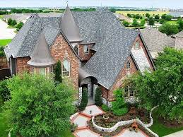 luxury brick home with spires and tile roof