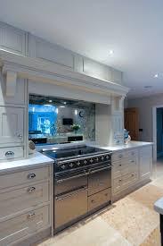 stainless steel electric cooker white kitchen cabinets metal handles antique mirror backsplash stone tile flooring ceiling lights