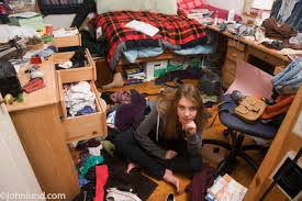 Picture Of A Very Messy Teenagers Bedroom. A Young Teen Girl Is Sitting On  The