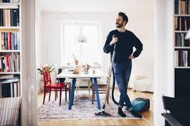 happy man standing with vacuum cleaner in dining room at home