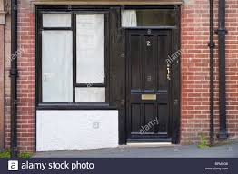 victorian paneled black painted wooden front door and window of brick built house in llandrindod wells powys mid wales uk