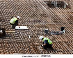 construction workers installing steel rebar beams for reinforced concrete building site stock photo rebar worker