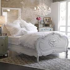 a simply stunning intricately detailed crystal chandelier seems to cast a romantic spell over this pretty bedroom pastel painted chests look lovely with