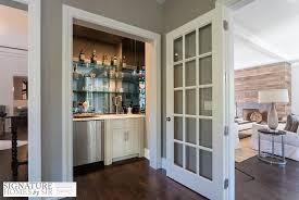 wet bar nook with glass shelves on mirrored backsplash