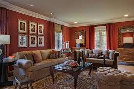 an eclectic living room features warm red walls paired with tan furniture the lovely wall hangings draw the eye around the room