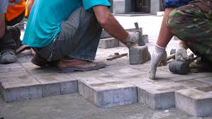 4k00 17workers spread stone paving slabs wearing white cloth gloves align top and knock a rubber mallet to better bonding between the stones