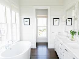 white dual vanity with shiplap walls