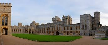 a photograph of a grey gothic quadrangle with a green grass square in the middle