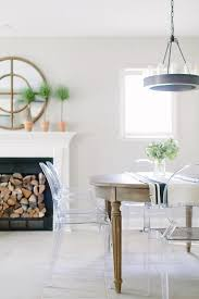 oval reclaimed wood dining table lined with ghost chairs illuminated by a ralph lauren roark 20 modular ring chandelier placed in front of a fireplace
