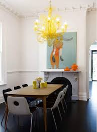 yellow chandelier over dining table and art above fireplace