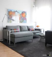 big modern sectional sofa with round glass tabele on dark rug along with curved floor lamp