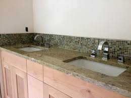 this bathroom remodel project features glass mosaic tile backsplashes with solid granite countertops and tub surround