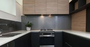 contemporary black kitchen with grey gl splashback