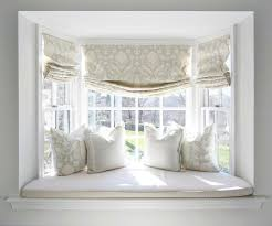 Cozy up a bay window with pretty curtains an upholstered seat cushion and a  few extra pillows. By Amelia Perez