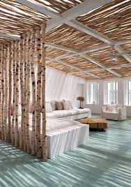 In an airy beautifully natural lit space, the usage of natural materials is  a must. Here actual slim wooden trunks have been used to form a barrier for  the ...