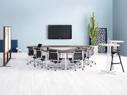 a meeting room featuring black eames aluminum group chairs around everywhere conference tables in a triangle