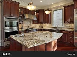 Kitchen With Granite Kitchen With Granite Island And Cherry Wood Cabinetry Stock Photo
