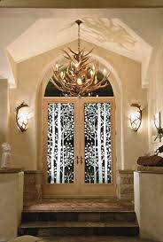 1 carved thermal unit front entry glass with aspen trees and leaf detail also shown fallow bell sconces and elk antler chandelier