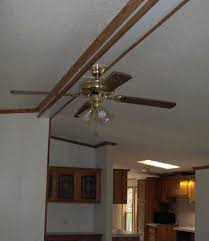along the center of the livingroom is the seam most manufactured homes have and a pretty ugly looking ceiling fan i removed the bottom row of molding and ceiling fans ugly