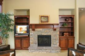 tv over fireplace and stone fireplace mantels with floating mantel shelf also fireplace scree and tea light candles with hardwood flooring and stacked stone