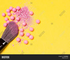 close up of makeup brush with crushed and whole shimmer blush pink color on yellow background unusual angle shallow depth of field copy e
