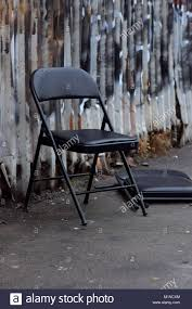 black metal folding chairs. Black Metal Folding Chairs On A Dirty White Sidewalk In Front Of Rusty Wall