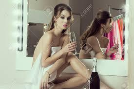 Sensual Girl Sitting In Bathroom Near Mirror With Bottle Of ...