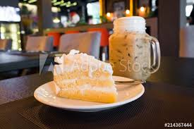 Coconut Cake With Young Coconut On Top Served With Iced Coffee In