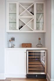 Here, a wine refrigerator and cabinet create the base of the bar. Above,  built-in shelving and glass-front cabinets ...