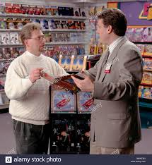 adult male s clerk showing a male customer a gaming software adult male s clerk showing a male customer a gaming software package in a retail store