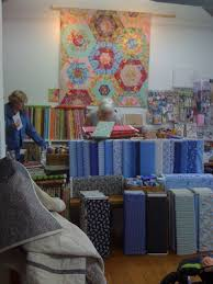 Quilt Inspiration: Quilting in New Zealand & The elegant Suzy Miller, who owns the shop, can be seen in the middle as  she cuts fabric. Adamdwight.com