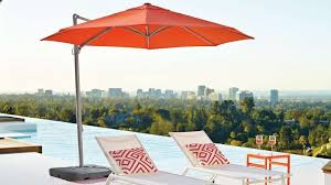 small orange cantilever patio umbrella with pool lounge chairs