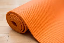 the yoga accessories extra thick deluxe yoga mat rolled up in orange on a wooden floor