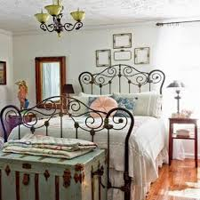 vintage white wall color and tulip styled chandelier for classic bedroom decorating ideas with black ornate bed frame