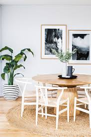 this coastal style dining room features white hans wegner wishbone chairs and a circular sisal rug