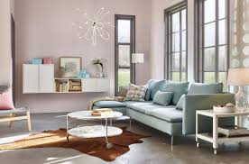 in this living room the blue sofa matches the light pink painting wall very much